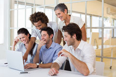 Business people laugh while looking at laptop Stock Photo