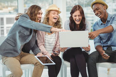 Business people laughing while pointing at laptop Stock Photos