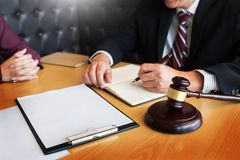 Business people and lawyers discussing contract papers sitting a. T the table. Concepts of law, advice, legal services Stock Image