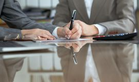Business people or lawyers signing contract at meeting. Close-up of human hands at work.  royalty free stock image