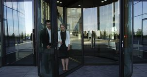 Business people leaving building. Two business people leaving building through spinning door and talking