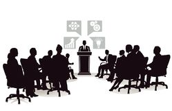 Business people at lecture. Silhouetted business people sat at lecture and discussion with person speaking at lectern with symbols in background Stock Photos