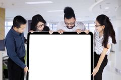 Business people looking at an empty white board with copy space. Business people lift an empty white board with copy space Stock Photography