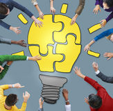 Business People with Light Bulb Jigsaw Symbol Stock Photos
