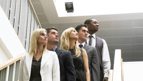 Business people in a line on stairs with thumbs up smiling at the camera Stock Image