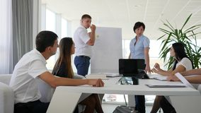 Business people listen to presentation of two people standing near flipchart offers ideas. In white conference room stock video footage