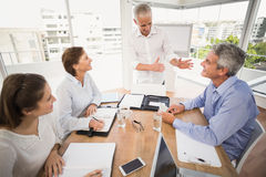 Business people listening to colleagues presentation Stock Image