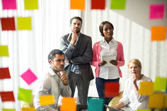 Business people looking at adhesive notes Royalty Free Stock Photography