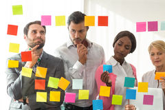 Business people looking at adhesive notes Stock Image