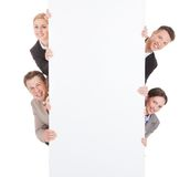 Business people looking from behind the blank billboard Royalty Free Stock Images