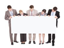 Business people looking at blank billboard. Full length of young business people looking at blank billboard over white background royalty free stock image