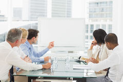 Business people looking at blank whiteboard in conference room Royalty Free Stock Photos