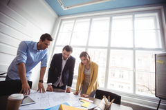 Business people looking at blueprint on table Stock Images