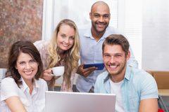 Business people looking at camera behind a laptop Royalty Free Stock Photography