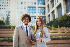 Business people looking at camera, holding digital tablet outdoor. Selective focus stock photos