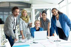 Business people looking at camera during meeting at conference room in a modern office. Front view of diverse business people looking at camera during meeting at royalty free stock photo