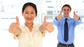 Business people looking at camera and showing thumbs up. In the office stock video