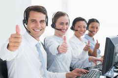 Business people looking at camera with thumbs up Stock Photos