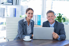 Business people looking at camera and using laptop. In office Stock Photography