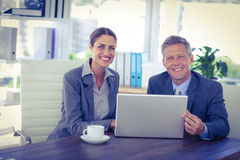 Business people looking at camera and using laptop Stock Image