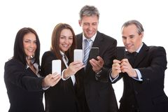 Business people looking at cell phones Stock Photos