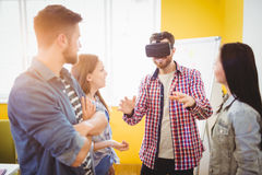 Business people looking at coworker wearing virtual reality headset. In creative office Stock Photo