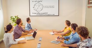Business people looking at diagram on screen in conference room royalty free stock photos