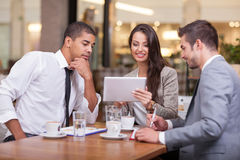 Business people looking at digital tablet in cafffee during a me Royalty Free Stock Photography