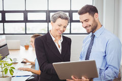 Business people looking in digital tablet at office. Happy business people looking in digital tablet while standing at office Royalty Free Stock Photo