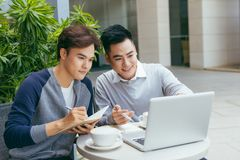 Business people looking at document and discussing while at cafe. Two businessmen working together on business report at coffee. Shop. - Image stock photos