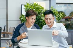 Business people looking at document and discussing while at cafe. Two businessmen working together on business report at coffee. Shop. - Image stock images
