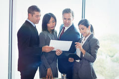 Business people looking at document while standing Royalty Free Stock Photos