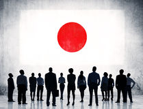 Business People Looking at Flag of Japan. Group of Business People Standing with a View of the National Flag of Japan Royalty Free Stock Images