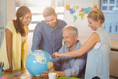 Business people looking at global in meeting room. Smiling business people looking at global in meeting room at creative office Royalty Free Stock Images