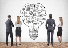 Business people looking at business idea sketch. Four young business people in suits standing together and looking at business idea sketch drawn on concrete wall royalty free stock images