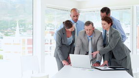 Business people looking at laptop computer during meeting stock footage