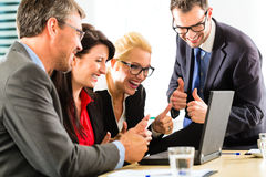 Business people looking at laptop with success Stock Image