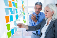 Business people looking at post it on the wall Royalty Free Stock Photos