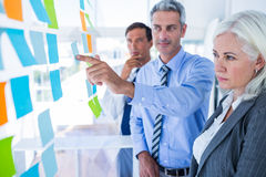 Business people looking at post it on the wall Royalty Free Stock Images