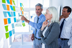 Business people looking at post it on the wall Stock Photos