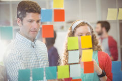Business people looking at post it on the wall Stock Photo