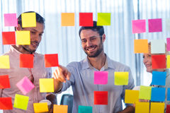 Business people looking at post it on the wall. In office royalty free stock photos