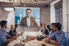 Business people looking at projector during video conference stock photos