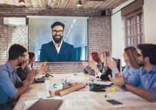 Business people looking at projector during video conference. In office stock photos