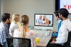 Business people looking at a screen during a video conference. In the conference room Stock Image