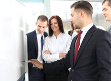 Business people looking at their leader while he explaining something. On whiteboard Royalty Free Stock Image