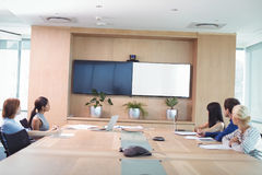Business people looking at whiteboard during meeting. In board room Stock Photography