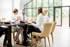 Business people during a lunch at the restaurant. Business people dressed in white shirts having fun sitting together during a business lunch with delicious stock image