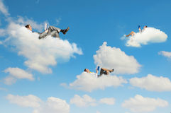 Business people lying on clouds Stock Images