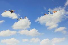 Business people lying on clouds Royalty Free Stock Image